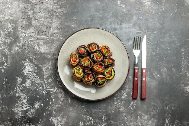Vue de dessus des rouleaux d'aubergines farcies sur une fourchette et un couteau ovales blancs sur une surface grise