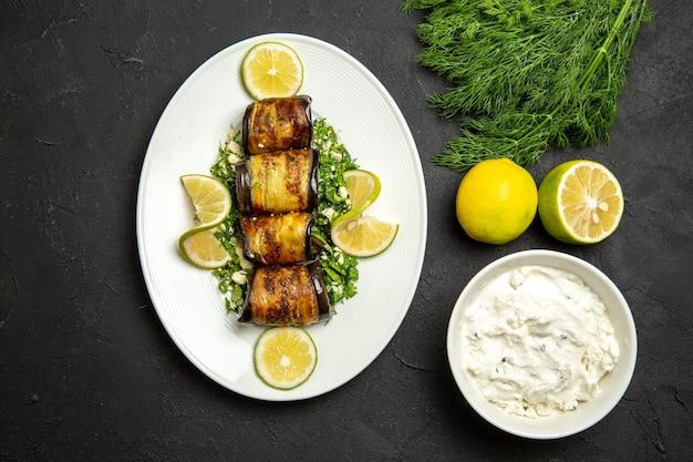 Vue de dessus des rouleaux d'aubergines salés plat cuit avec des tranches de citron sur un sol sombre dîner à l'huile plat de repas de cuisson