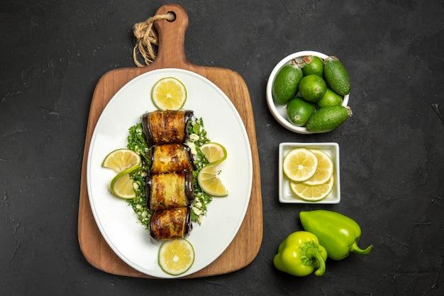 Vue de dessus rouleaux d'aubergines salés plat cuit avec des tranches de citron sur la surface sombre dîner cuisson repas plat d'huile d'agrumes