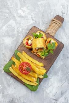 Vue de dessus des rouleaux de pâté de légumes avec des frites sur une surface blanche