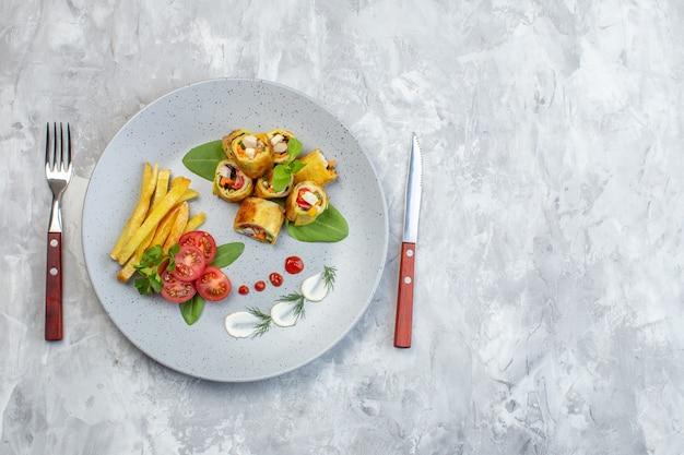 Vue de dessus des rouleaux de pâté de légumes avec des tomates et des frites à l'intérieur de la plaque sur une surface blanche
