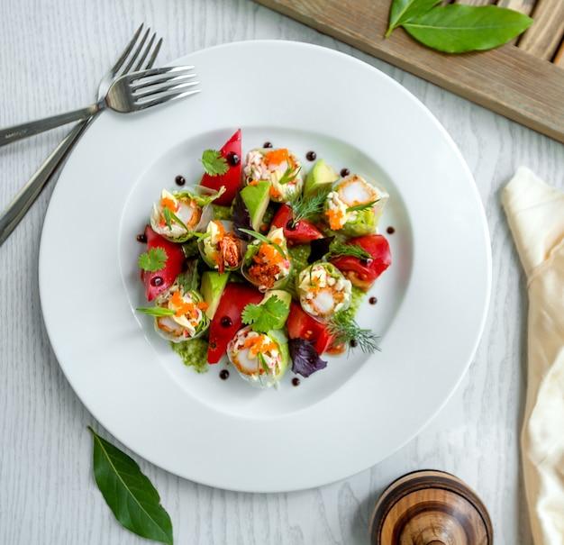 Vue de dessus de rouleaux de printemps demi-coupés aux crevettes, laitue servie avec avocat