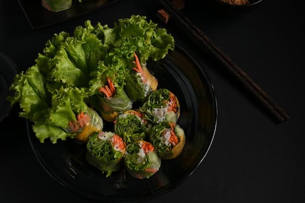 Vue de dessus des rouleaux de printemps vietnamiens et légumes en apéritif asiatique fond sombre