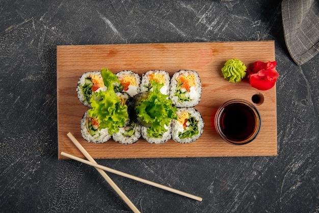 Vue de dessus sur les rouleaux de riz aux algues gimbap sur la planche de bois avec sauce soja