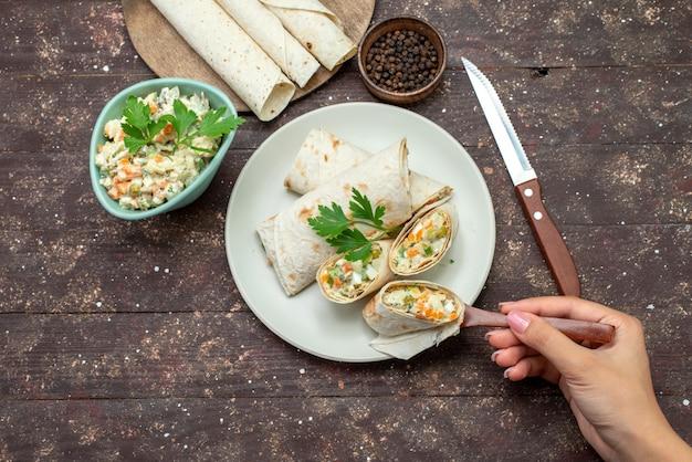Vue de dessus des rouleaux de sandwich lavash en tranches avec de la salade et de la viande à l'intérieur avec de la salade sur le bureau en bois snack-repas sandwich