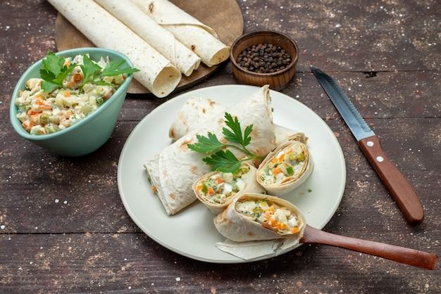 Vue de dessus des rouleaux de sandwich lavash en tranches avec de la salade et de la viande à l'intérieur avec de la salade sur le sandwich au repas de bureau en bois