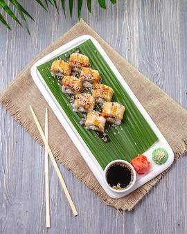 Vue de dessus des rouleaux de sushi à l'anguille avec du wasabi au gingembre et de la sauce de soja sur une plaque