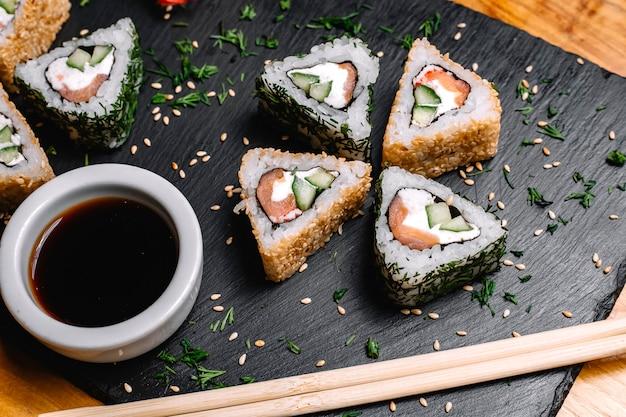 Vue de dessus rouleaux de sushi au saumon avec sauce soja
