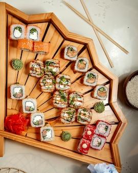 Vue de dessus des rouleaux de sushi mis en place sur un plateau à sushi en bois en forme d'éventail