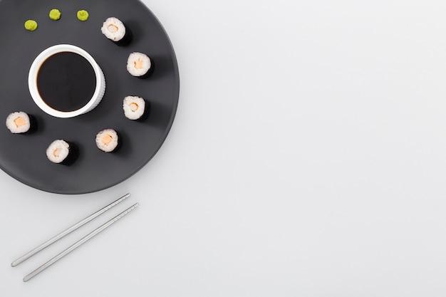 Vue de dessus rouleaux de sushi et sauce soja avec espace copie