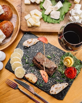 Vue de dessus rouler la viande avec des tranches de citron et un verre de vin rouge