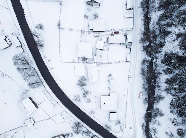 Vue de dessus de la route près des maisons couvertes de neige et de la rivière de montagne qui coule à proximité.