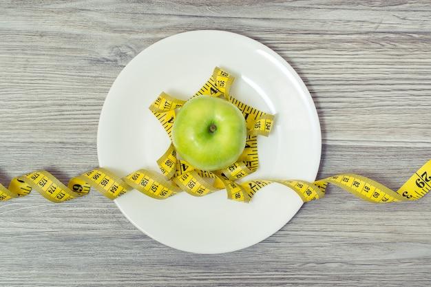 Vue de dessus sur un ruban à mesurer enroulé autour d'une pomme sur une plaque blanche