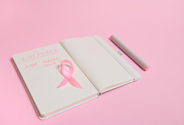 Vue de dessus d'un ruban rose, sur un agenda ouvert avec des inscriptions rappelant un examen médical. 1er octobre, journée mondiale du cancer du sein, journée rose d'octobre, journée mondiale contre le cancer, national cancer survivor say.
