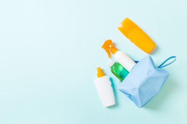 Vue de dessus d'un sac de cosmétiques féminin rempli de spray de crème solaire, d'écran solaire, de crème solaire et de lotion pour le corps et de crème spf sur fond bleu avec espace de copie. directement au dessus. concept d'été lumineux.