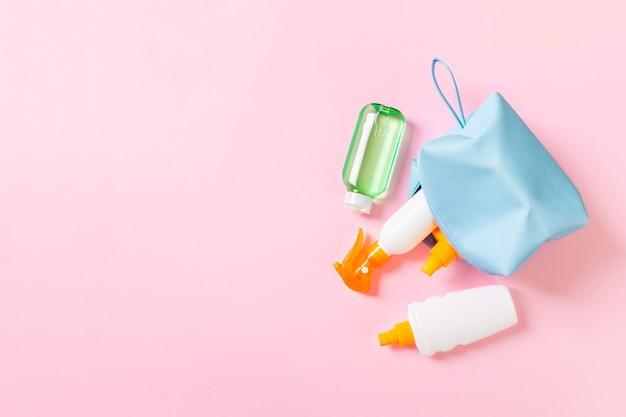 Vue de dessus d'un sac de cosmétiques féminin rempli de spray de crème solaire, d'écran solaire, de crème solaire et de lotion pour le corps et de crème spf sur fond rose avec espace de copie. directement au dessus. concept d'été lumineux.