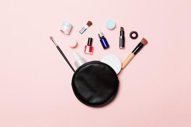 Vue de dessus de sac de cosmétiques avec des produits de maquillage renversés sur rose