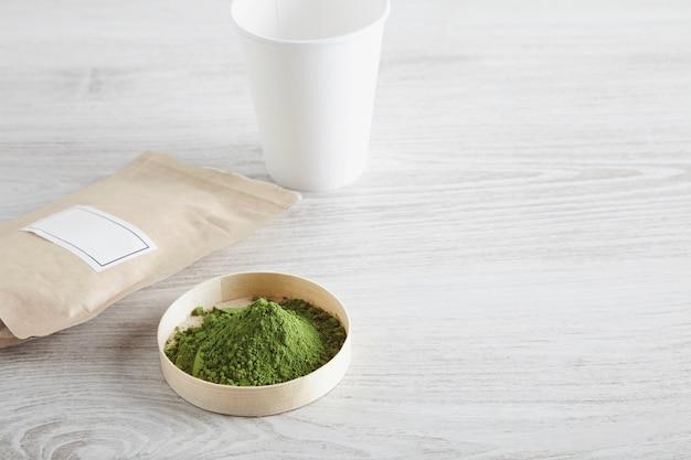 Vue de dessus sac de papier brun artisanal, verre à emporter et poudre de thé matcha biologique de qualité supérieure dans une boîte sur une table en bois blanche isolée sur fond simple. prêt à préparer, présentation de vente.