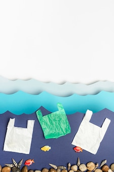 Vue de dessus des sacs en plastique et des roches dans l'océan de papier