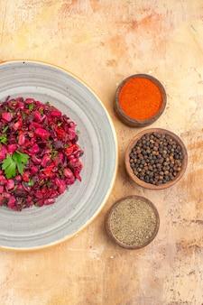 Vue de dessus de la salade sur une assiette en céramique avec du poivre noir moulu du curcuma au poivre noir sur un fond en bois avec place pour copie