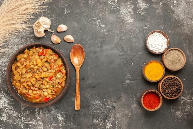 Vue de dessus de la salade d'aubergines rôties dans un bol de bouteille d'huile ail cuillère en bois différentes épices dans des bols sur une surface sombre
