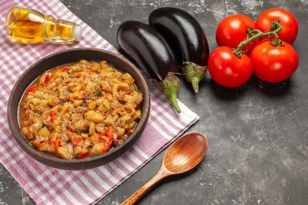 Vue de dessus de la salade d'aubergines rôties dans un bol cuillère en bois tomates aubergines huile bouteille sur surface sombre