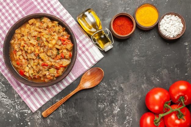 Vue de dessus de la salade d'aubergines rôties dans un bol d'huile, cuillère en bois et tomates sur une surface sombre