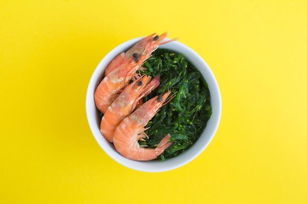 Vue de dessus de la salade aux algues et crevettes rouges dans le bol blanc sur fond jaune. fermer.