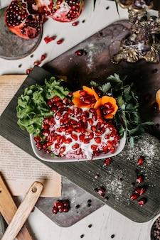Vue de dessus de la salade de betteraves rouges avec sauce mayonnaise et grenade sur une planche de bois
