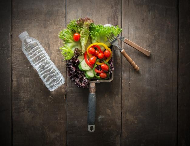Vue de dessus de salade avec une bouteille d'eau