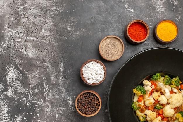 Vue de dessus salade de brocoli et de chou-fleur dans un bol noir différentes épices dans des bols sur l'espace libre de surface sombre