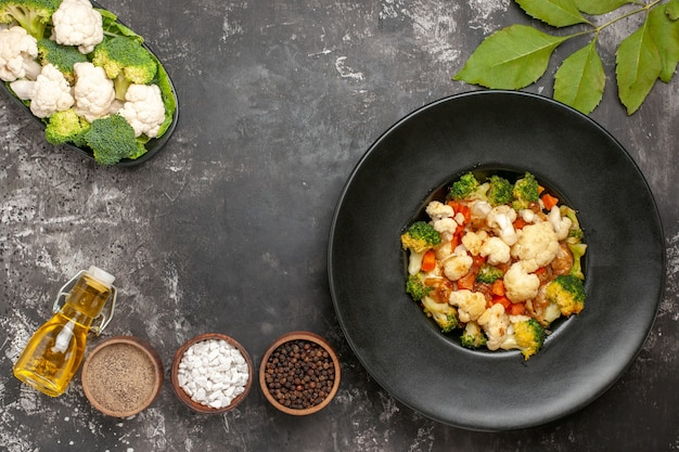 Vue de dessus salade de brocoli et de chou-fleur dans un bol noir différentes épices dans des bols de légumes crus d'huile sur une plaque sur une surface sombre