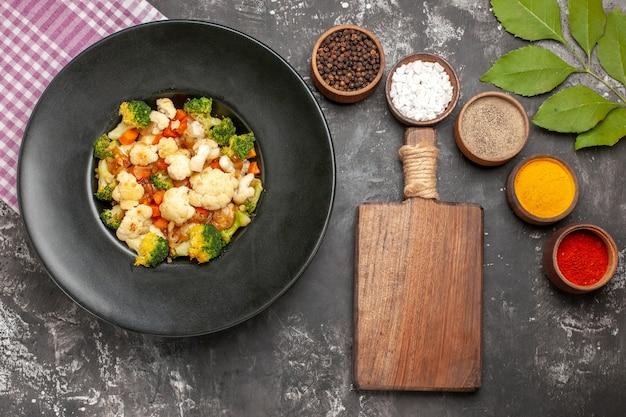 Vue de dessus salade de brocoli et de chou-fleur dans un bol noir serviette à carreaux rose et blanc différentes épices une planche à découper sur une surface sombre