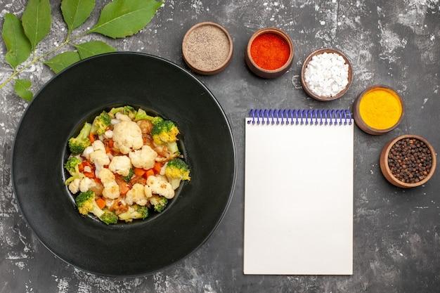 Vue de dessus salade de brocoli et de chou-fleur sur plaque ovale noire différentes épices dans de petits bols sel de mer au curcuma poivrons un cahier sur une surface sombre