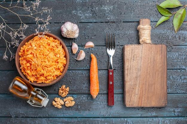 Vue de dessus salade de carottes râpées à l'ail et aux noix sur le bureau rustique bleu foncé salade santé légumes couleur régime mûr