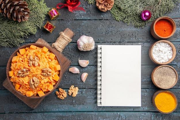 Vue de dessus de la salade de carottes râpées avec des noix et des assaisonnements sur le bureau bleu foncé salade d'aliments naturels régime couleur de noix