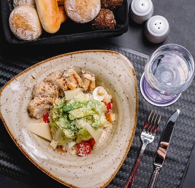 Vue de dessus de la salade césar au poulet servie avec du pain