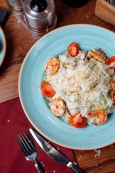 Vue de dessus de la salade césar aux crevettes et au parmesan sur la table