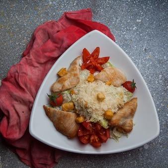 Vue de dessus salade césar avec tomate et chiffon dans une assiette triangulaire