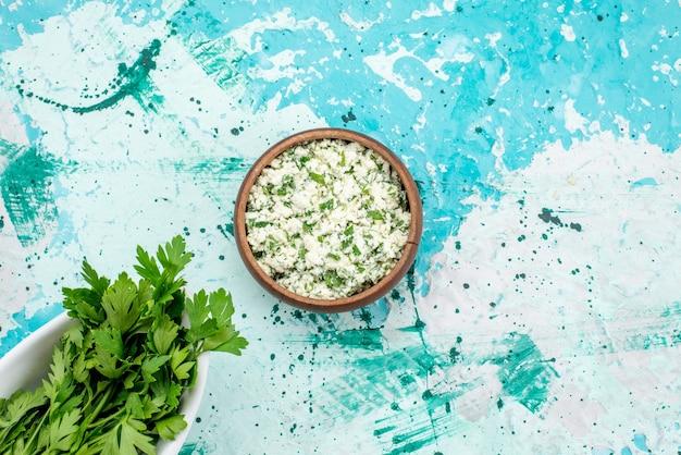 Vue de dessus de la salade de choux frais tranchés avec des verts à l'intérieur d'un bol brun sur bleu vif, salade de légumes verts fraîcheur snack