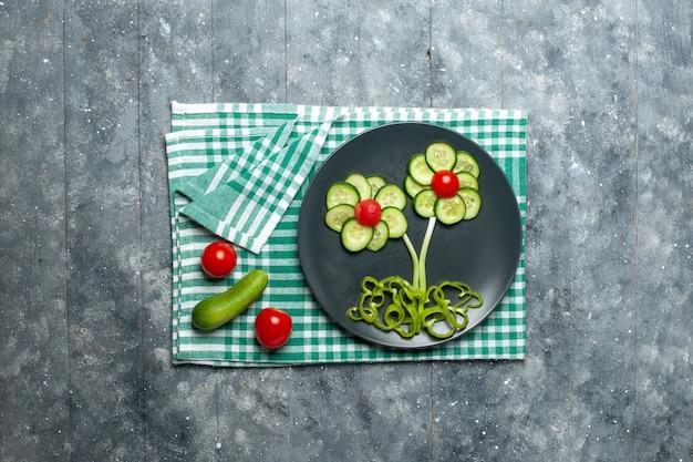 Vue de dessus salade conçue de fleurs de concombres frais sur espace gris