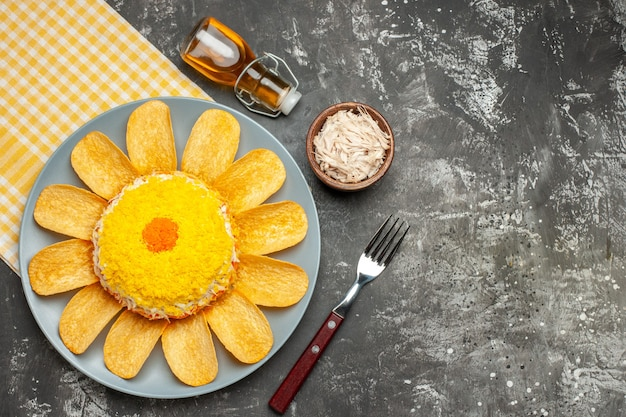 Vue de dessus de la salade sur le côté gauche avec une serviette jaune en dessous avec une bouteille d'huile de fourche à fromage sur le côté sur table gris foncé