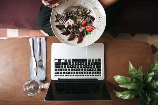 Vue de dessus de la salade dans les mains et le verre avec un couteau et une fourchette sur la table au restaurant