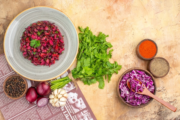 Vue de dessus de la salade fraîche sur une assiette en céramique avec des oignons rouges, un bouquet de persil à l'ail et du poivre noir, du poivre moulu, du curcuma et du chou rouge dans un bol en bois sur un fond clair avec un lieu de copie