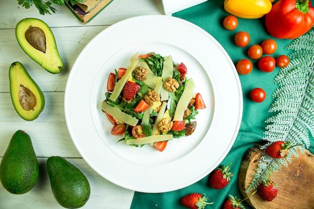 Vue de dessus de la salade fraîche au parmesan, avocat, noix, tomates cerises et fraises dans un bol blanc