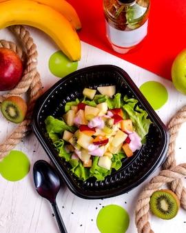 Vue de dessus de salade de fruits avec pomme kiwi et bananes dans une boîte de livraison