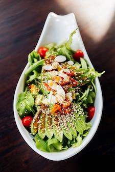 Vue de dessus d'une salade japonaise à l'avocat, à la tomate, au chêne vert, aux amandes et au sésame, garnie de vinaigrette au sésame.
