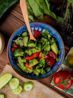 Vue de dessus de la salade de légumes avec concombre coupé et tranché tomate basilic épinards sur bois