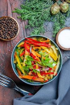 Vue de dessus salade de légumes dans un bol châle bleu outremer fourchette de poivre noir sur table rouge foncé