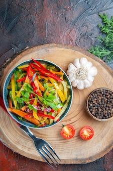Vue de dessus salade de légumes dans un bol fourche ail poivre noir sur planche rustique branche de sapin sur table rouge foncé
